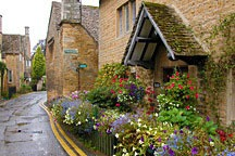 colorful frontage garden tucked between tan stone wall of house and street paving in Bourton-On-The-Water in England