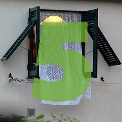 the number 5 superimposed over a window with open shutters and a lace curtain in Corniglia of the Cinque Terre in Italy