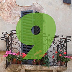 the number 9 superimposed over a picture of a balcony with flowerpots on an ancient stucco building in Pienza, Italy