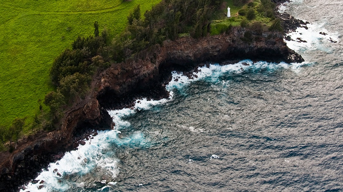 northern Hawaiian shoreline battered by Pacific waves under the watchful eye of solitary white lighthouse