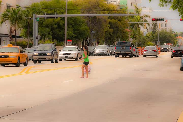 lone woman surrounded by speeding traffic as she attempts to cross treacherous stretch of Alton Road on South Beach