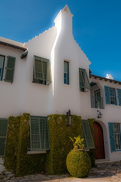 chimney of house in Alys Beach, Florida set against scrolled gable - chimney is punctured by a thin window above and skirted by a wall of green at the street level