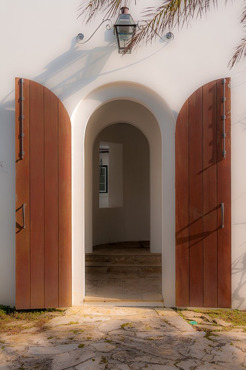 Arched wood double doors surmounted by scroll-supported copper carriage light open wide to reveal inner arch, and beyond that, a glimpse of Alys Beach courtyard