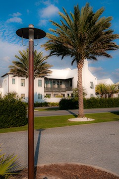 mahogany street light pole working with palm tree to frame a view of porch and courtyard of home in Alys Beach, Florida
