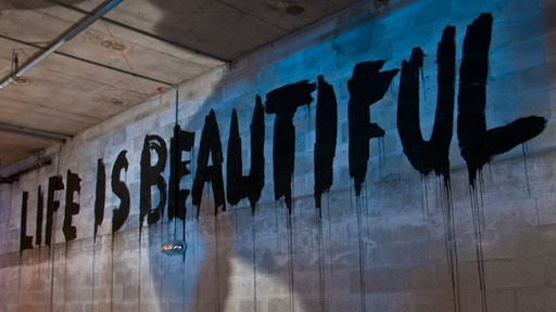 """Life is Beautiful"" splattered in black paint on concrete block wall at Art Basel 2011 in Miami Beach"