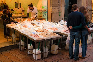 couple shopping at fish market in Bologna, Italy