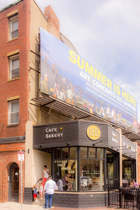 one-story liner building used for cafe & bakery turns a corner nicely in Boston, surmounted by a huge billboard