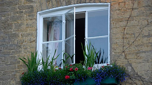 window in stone wall in Bourton-On-The-Water in the south of England