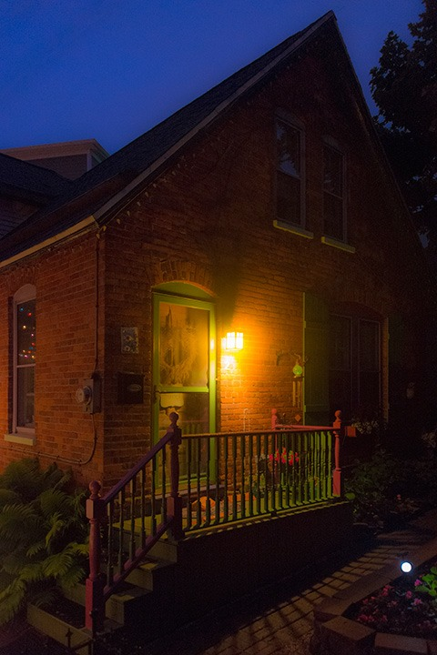 warm yellow glow of the porch light illuminates this tiny cottages front porch, painted a festive red and green, while night draws close around