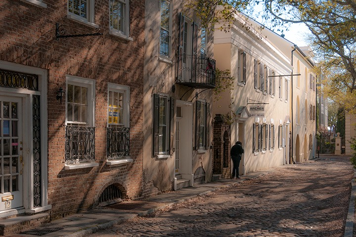 morning sunshine spilling across cobbled Charleston street lined by townhouses