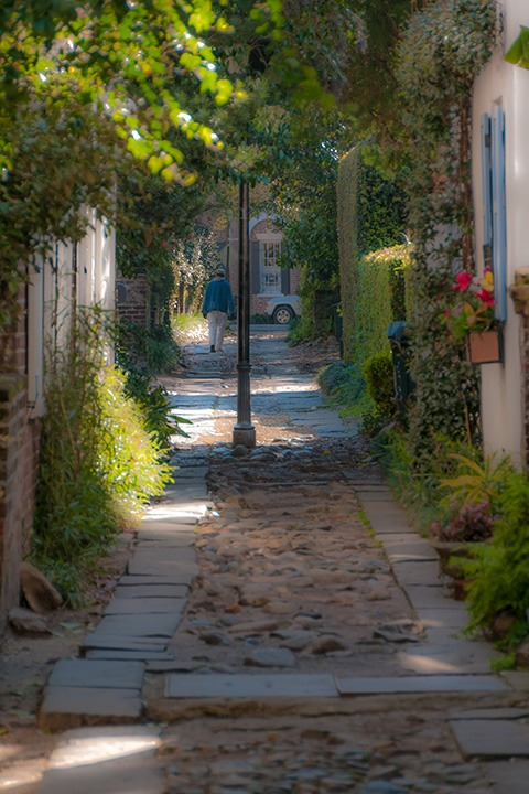 man walking in the distance down roughly-cobbled Charleston passage