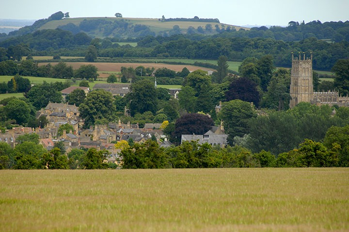 Chipping Camden seen from nearby meadows, and set against a lonely hilltop beyond