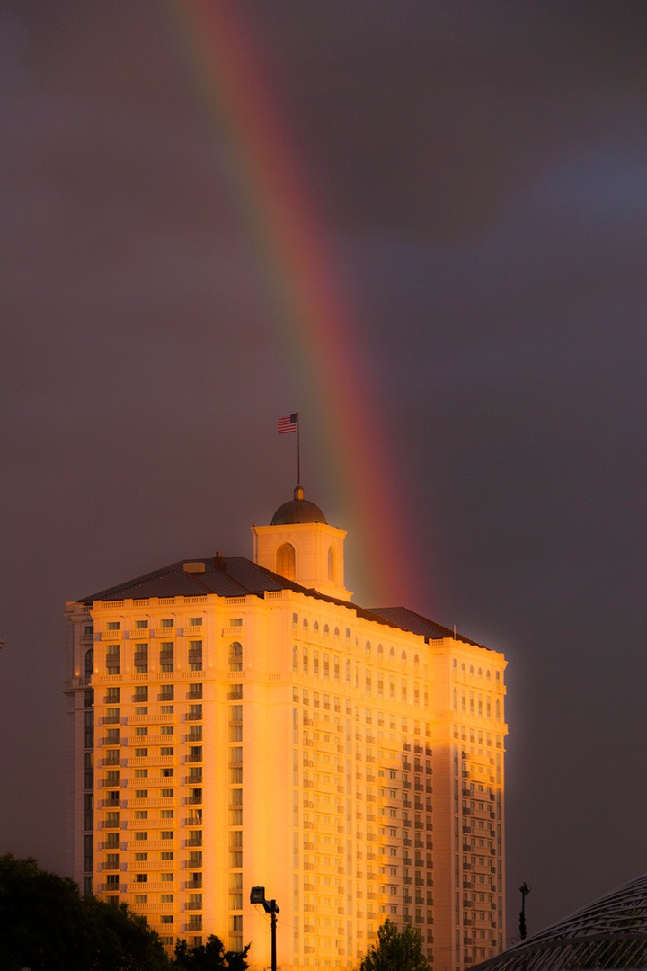 CNU21's venue, Salt Lake City's Grand America Hotel, glowing golden in last rays of sunset with rainbow behind set against clouds of the receding storm