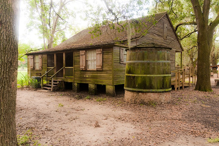 wood clapboard Acadian Cottage stands side-by-side with its rainwater cistern on the outskirts of Destrehan Plantation outside New Orleans