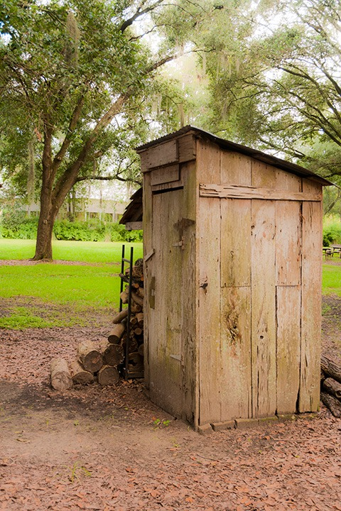 Destrehan Plantation outhouse stands silent beside a woodpile at the edge of a tree-shadowed green