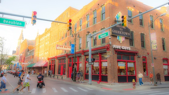 Greektown street corner bathed in warm evening light as residents & visitors flood onto the streets