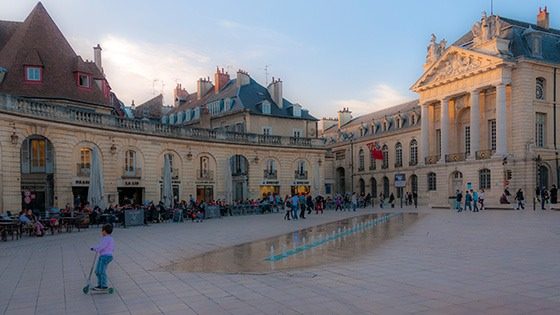 child rolling through plaza at sunset in Dijon, France with diners lining arcade at the edge and last rays of sunlight illuminating classical facade in golden glow
