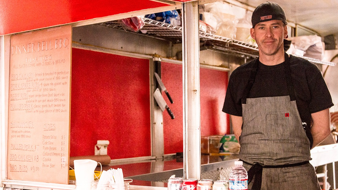 Sam Mouzon inside his Dinner Bell Barbecue food cart in Portland, Oregon, moments after opening for the first time