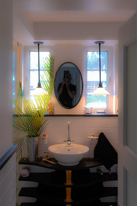 bathroom wall reflects the form of the face, with two narrow windows for eyes (lit by two pendant lights in the evening), an oval mirror for a nose, and white porcelain sink with chrome fittings for a mouth
