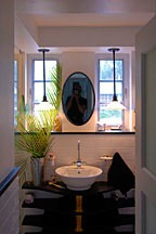 view into bathroom, with sink centered under elliptical mirror flanked by two pendant lights in front of two windows
