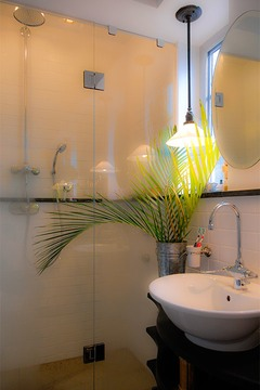 palm leaves in corrugated steel vase set against shower glowing softly through its minimal glass wall