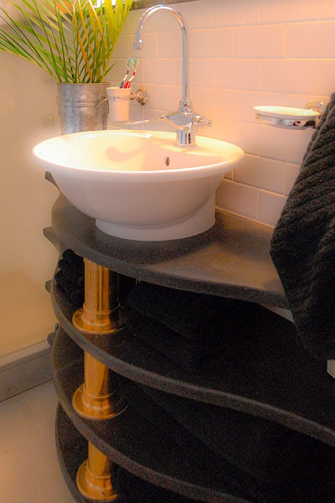 four black soapstone shelves curve along a bathroom wall, supported at their greatest extension by thick copper pipes