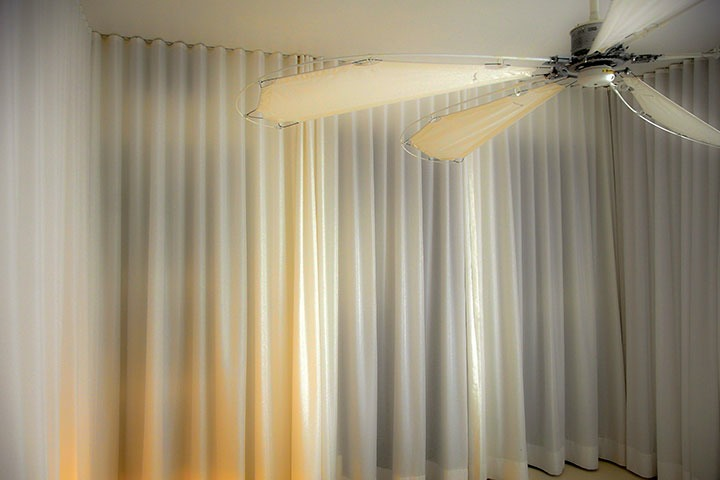 white curtains flow across a wall stirred by faint breezes of enormous ceiling fan constructed of fishing poles and sail cloth