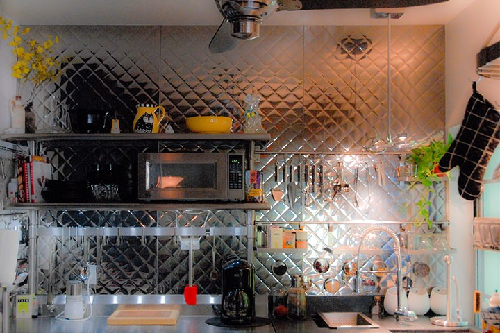 stainless steel kitchen tools and baker's rack sit against wall of pleated stainless steel panels like the ones found in classic deco diners