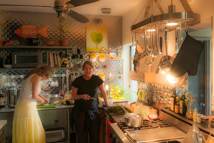 two sisters prepare dinner in kitchen glowing with warm light sparkling off stainless steel everywhere
