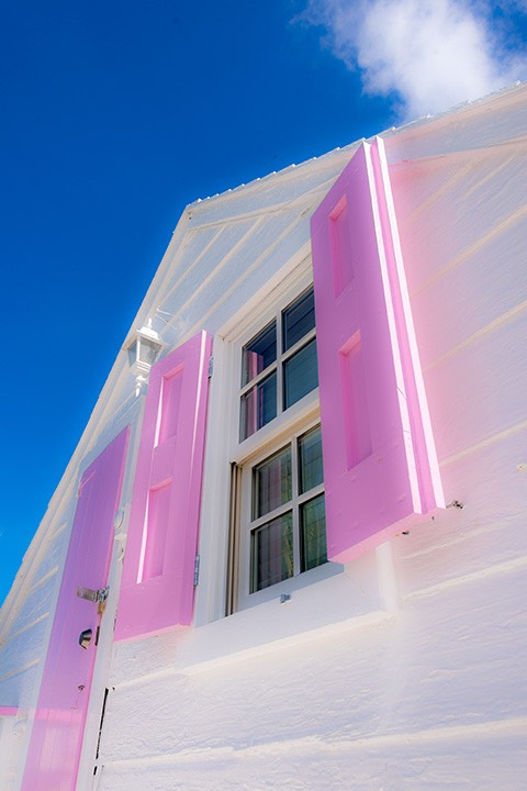 intense pink-shuttered door and window set against white gable stretch toward the sky above Dunmore Town on Harbour Island in the Bahamas