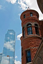 Richardsonian Romanesque red stone building in foreground with glass skyscraper in background