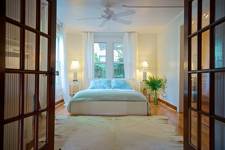 generous white linen curtains tumble around the bed, lit both from the pair of lamps standing like sentinels beside the bed and also from the light of the garden over the headboard beyond
