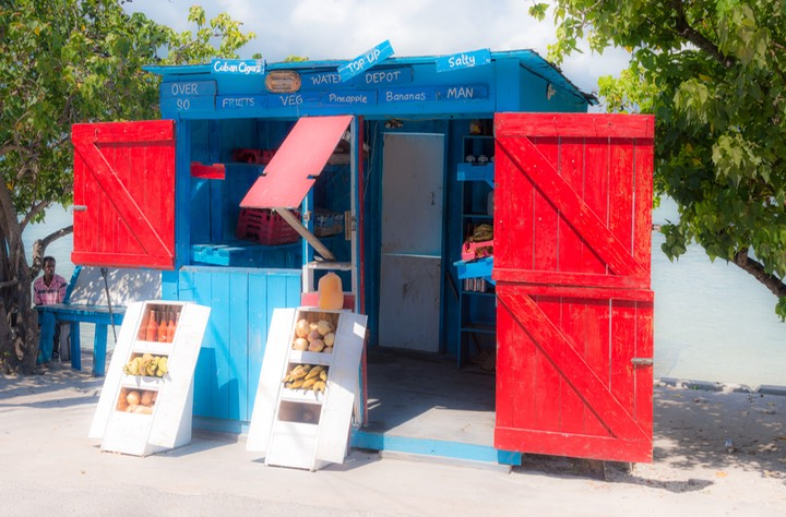tiny single-crew grocery store with glistening red shutters opened against sea-blue shop structure on Bay Street, Dunmore Town on Harbour Island in the Bahamas