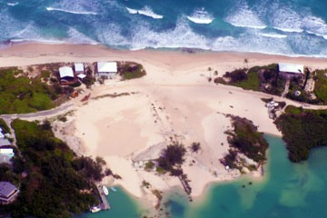 dune at Elbow Cay, Abaco, Bahamas breached by storm surge of Hurricane Irene, destroying houses behind it