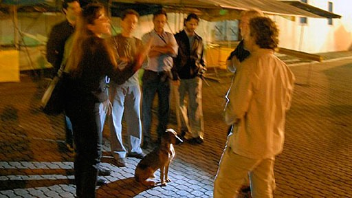 people debating an issue at night on the streets of Embu, Brazil while a dog sits in the center of the circle