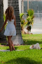 woman in a white dress walking her little white dog in Flamingo Park on South Beach