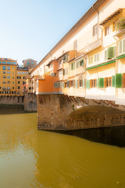 Florence's Ponte Vecchio bridge glows in the warm Tuscan sun as the green river slips by below