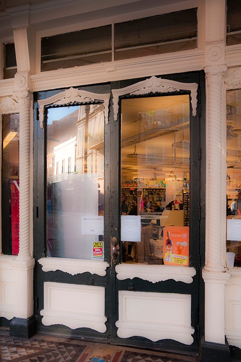 ornamental black & white double doors in New Orleans' French Quarter open to grocery