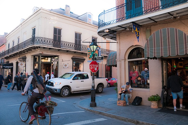 French Quarter intersection with bicyclist and driver negotiating right-of-way, serenaded by street musician sitting against the corner building
