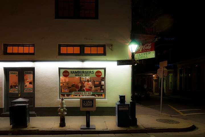 Clover Grill in New Orleans' French Quarter glows softly orange from within, while lit by blue-white light of corner street lamp against the gathering night