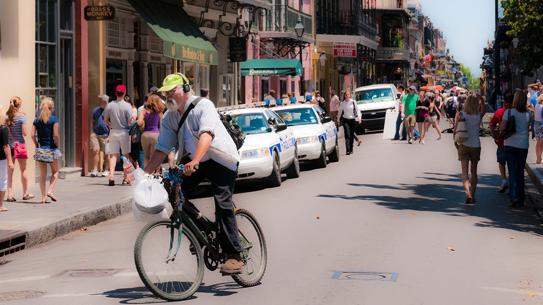 bicycle rider leaning into his turn off French Quarter street thronged by visitors, with green-sheathed cast iron galleries in the distance