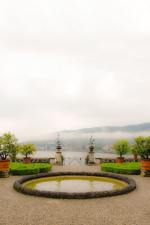 garden pond sits on Isola Bella, Italy against a background of clipped shrubs, potted trees, stone gates, with Lago Maggiore dividing the scene from mountains beyond