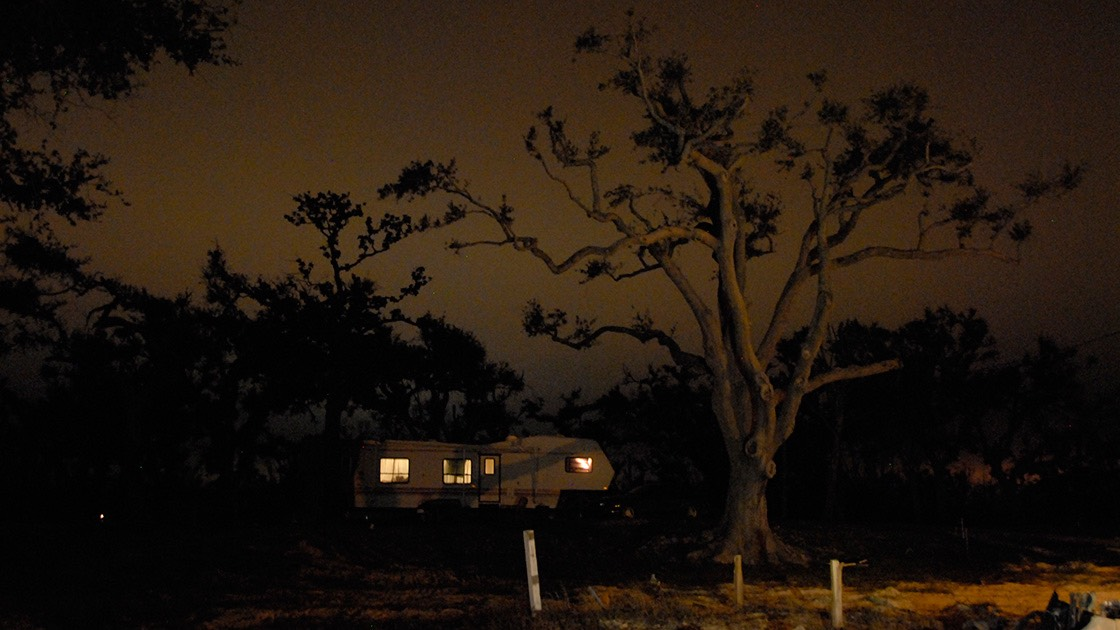 lone FEMA trailer glows like a jack-o-lantern under the spreading branches of a Mississippi live oak spreading against the softly glowing night sky in the wake of Katrina