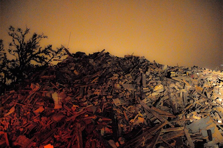 mountain of rubble in Gulfport, Mississippi glows eerily in evening light in the wake of Katrina
