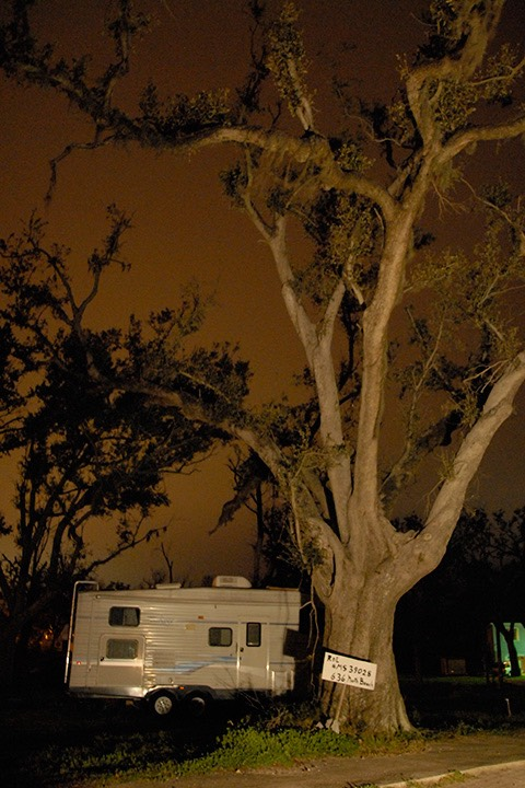 FEMA trailer hides its nose behind a massive Mississippi oak tree, which is silhouetted against the brown glow of the night sky