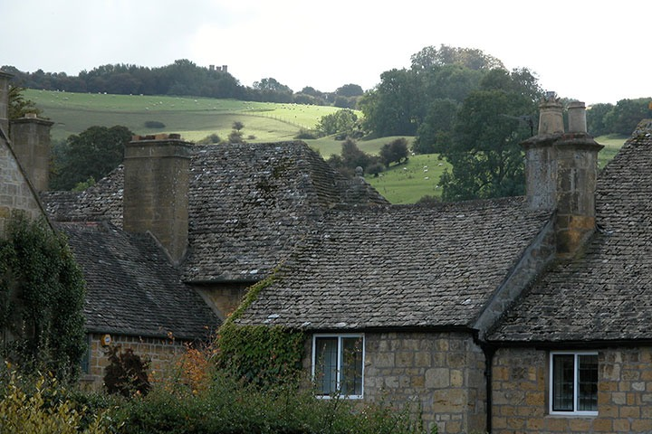 view from High Street to sheep grazing on rolling meadows outside Broadway, in the Cotswolds of England