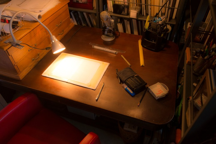 drawing table is illuminated with the warm glow of a task lamp snaking from its clamped perch on an adjacent drawing file