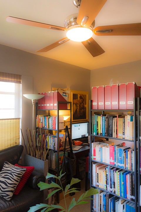 home office in a corner of a living room, partitioned by bookshelves