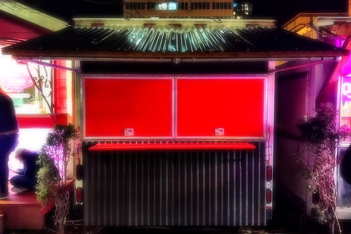 night lights glisten on the corrugated canopy roofing of Dinner Bell Barbecue food cart in Portland, Oregon, with window shutters glowing red just below