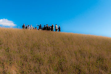 group of people standing on grass-covered hillside at La Bandita in Tuscany